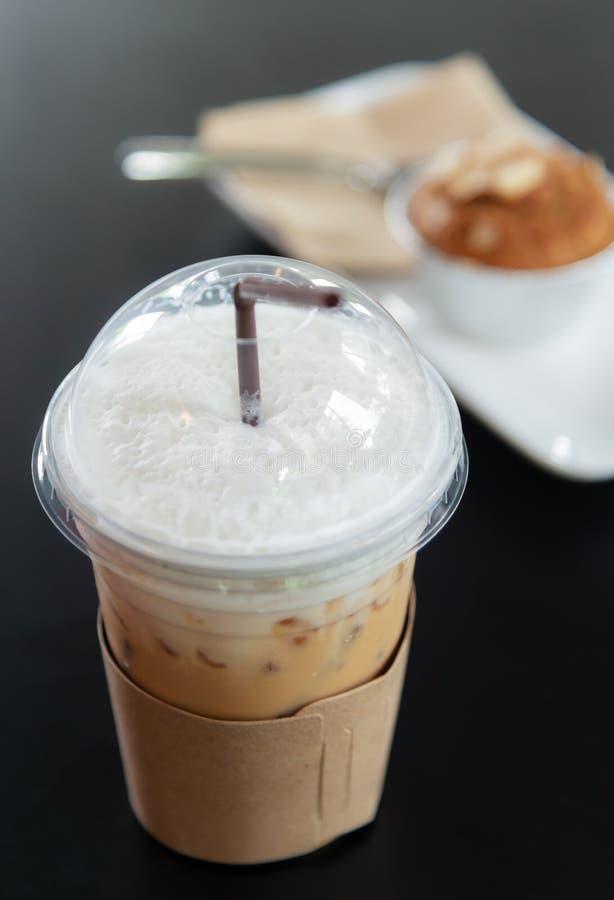 Cappuccinoiskaffe i ett exponeringsglas på den mörka trätabellen arkivfoton