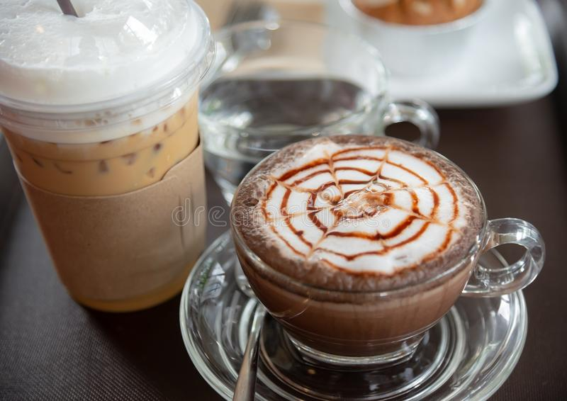 Cappuccinokaffe med is mjölkar te på trätabellen arkivbild