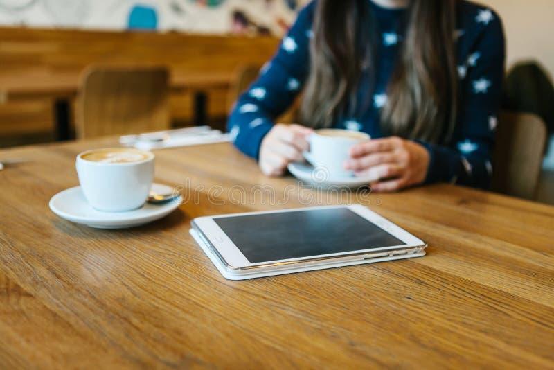 Cappuccinokaffee in einem Becher auf dem Tisch nahe bei der Tablette Entspannung oder Treffen in einem Café Das Mädchen wartet lizenzfreie stockfotografie