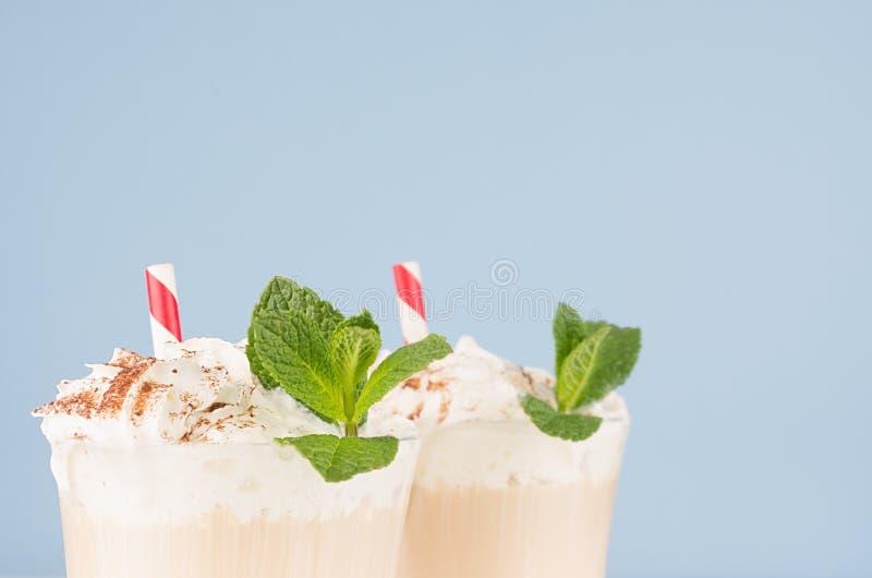 Cappuccinokaffee mit Schlagsahne, grüne Minze, Kakaopulver, rotes Stroh im transparenten Becher, Nahaufnahme, Details, Oberteil stockbild