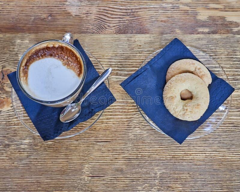 Cappuccinokaffekopp och kakor på trätabellen royaltyfri bild