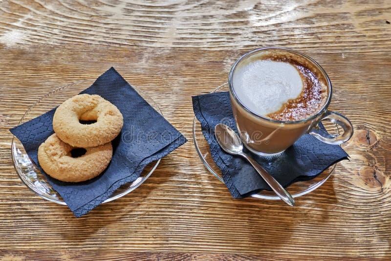 Cappuccinokaffekopp och kakor p? tr?tabellen fotografering för bildbyråer