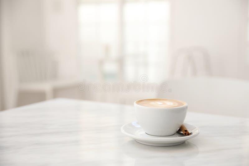 Cappuccinokaffekoppen på vit marmorerar tabellen royaltyfria bilder