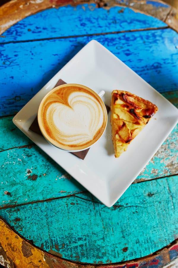 Cappuccinokoffie en appeltaart op kleurrijke groene en blauwe koffielijst royalty-vrije stock foto's