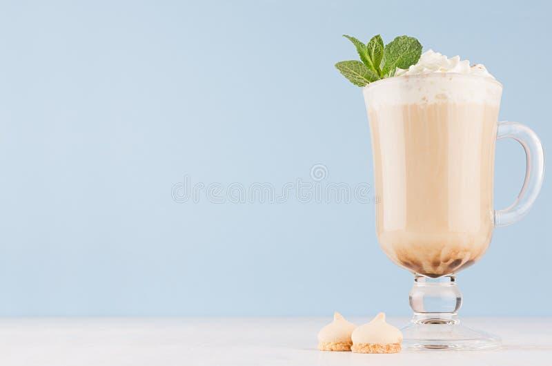 Cappuccinokoffie met slagroom, groene munt, koekjes in transparant glas met handvatten op zachte blauwe muur en witte houten raad royalty-vrije stock foto
