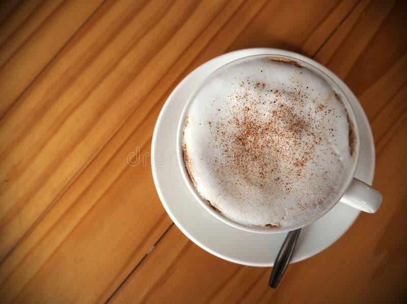 Cappuccinokoffie in witte kop op houten lijst, Hoogste mening royalty-vrije stock foto