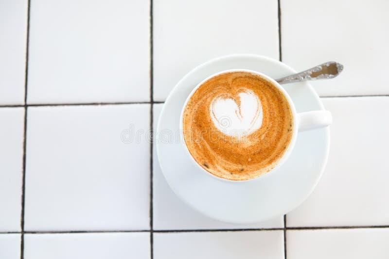Cappuccinokopp på belagd med tegel vit tabellbakgrund Skum dekoreras med kanelbrun hjärta kopiera avstånd Top beskådar arkivfoto