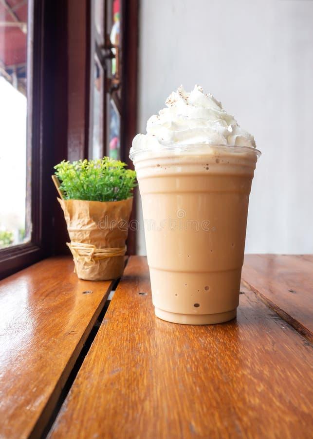 Cappuccinomengsel in plastic kop Gediend op houten lijst in koffie Favoriet menu van cafeïnedrank royalty-vrije stock afbeeldingen