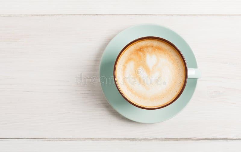 Cappuccinoskum, bästa sikt för kaffekopp på vit wood bakgrund royaltyfri bild