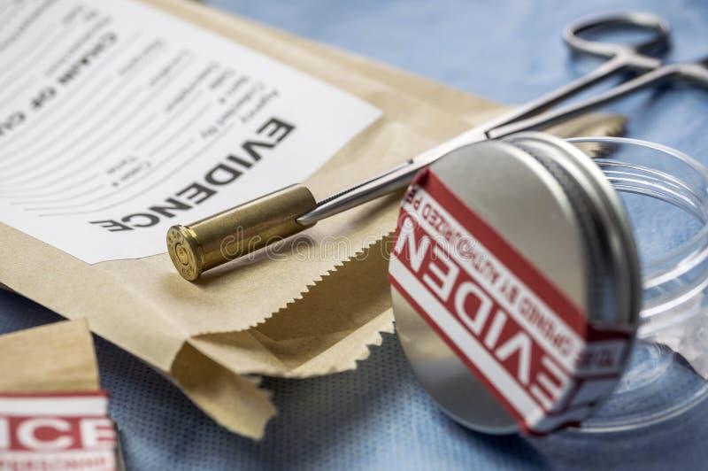 Cappuccio della pallottola accanto ad una borsa della prova in laboratorio balistico immagini stock