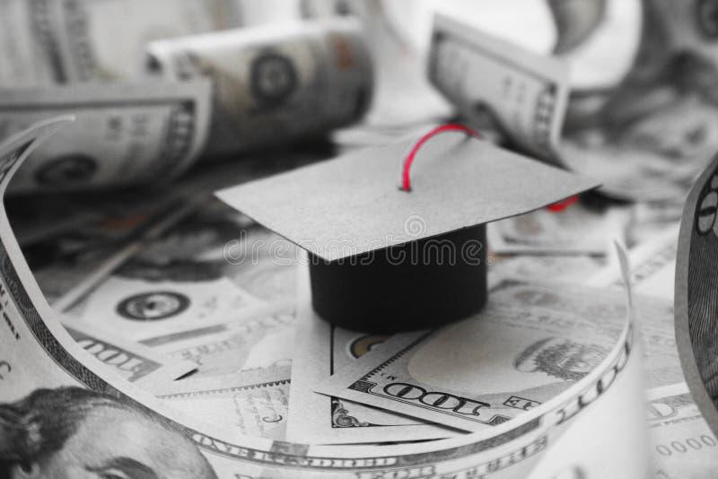 Cappuccio di graduazione dell'istituto universitario di Loan Debt With dello studente su soldi in bianco e nero immagini stock