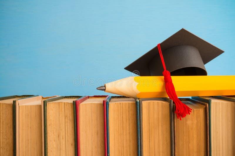 Cappuccio di graduazione e grande matita sopra i libri sul backgr blu della parete immagini stock libere da diritti