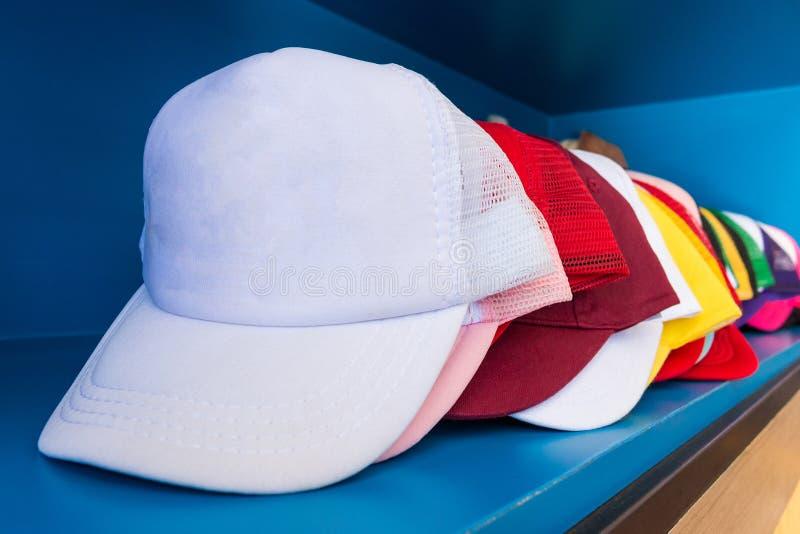 Cappuccio variopinto sul fondo blu dello scaffale Baseball di modo o cappello del hip-hop immagini stock
