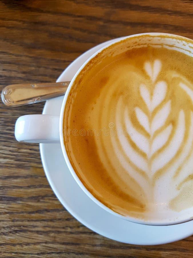 Cappuchino kaffe i den vita porcellan koppen och tefatet med sked a fotografering för bildbyråer