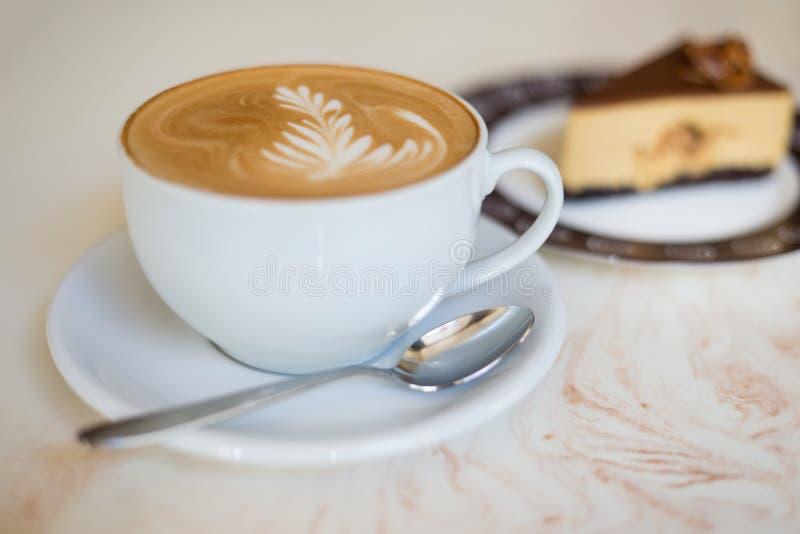Cappuchino of latte coffe in een witte kop met een cake stock foto