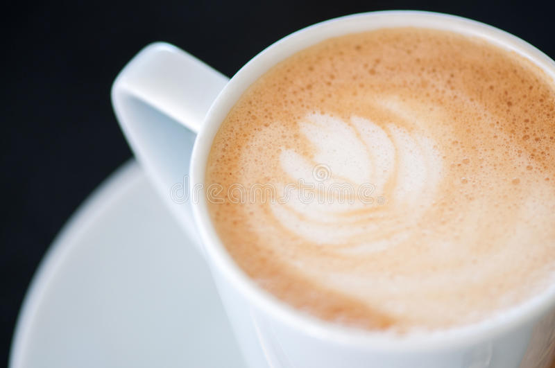 Cappuchino or latte coffe in a white cup on a dark background stock images