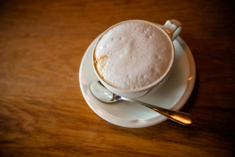 Cappuchino or latte coffe in a white cup with foam on wooden board. Morning energy drink isolated on dark wooden royalty free stock photography
