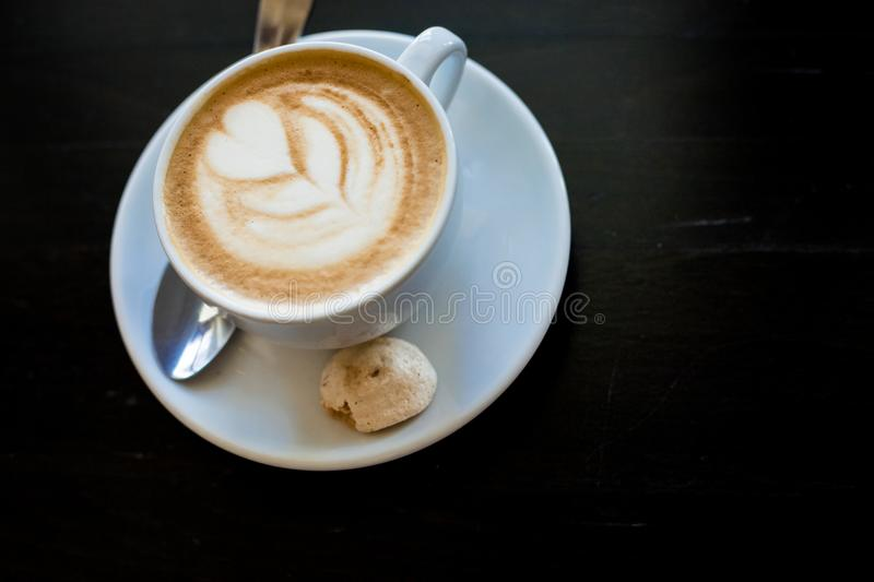Cappuchino or latte coffe in a white cup with heart shaped foam on wooden board. Morning energy dring isolated on dark royalty free stock photos
