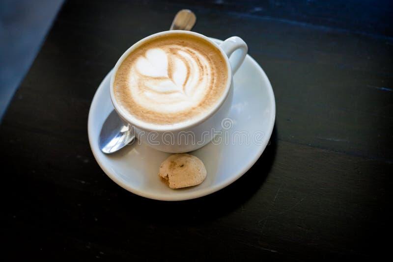 Cappuchino o coffe del latte en una taza blanca con espuma en forma de corazón y las galletas, bebida de la mañana en la tabla de fotos de archivo libres de regalías