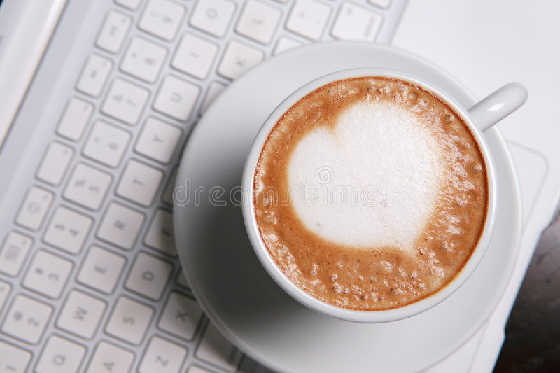 Cappucino with heart shape. On pc's keyboard royalty free stock photography