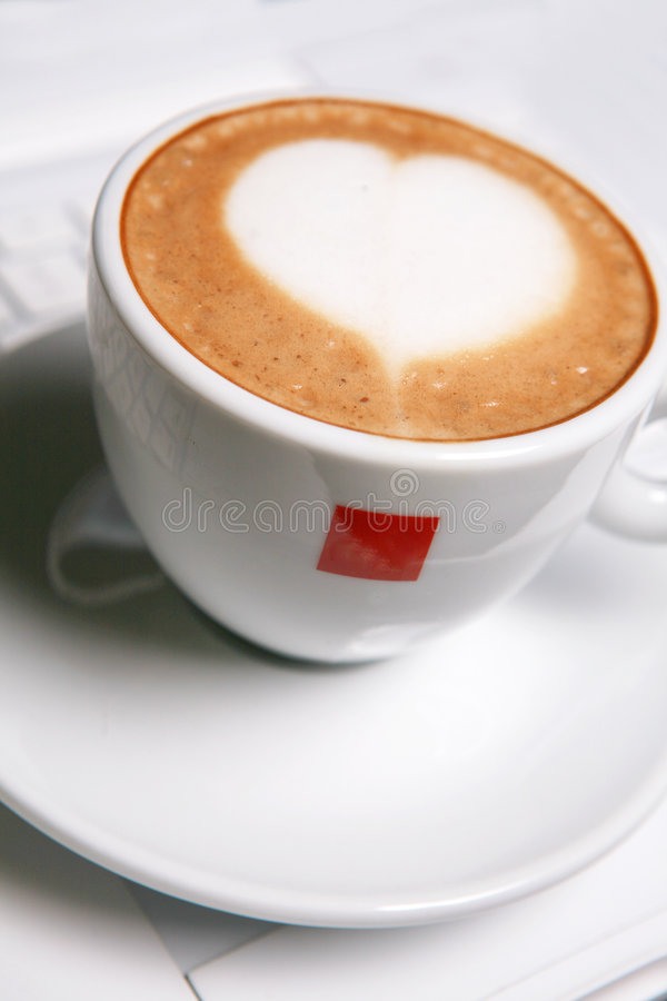 Cappucino with heart shape. On pc's keyboard royalty free stock images