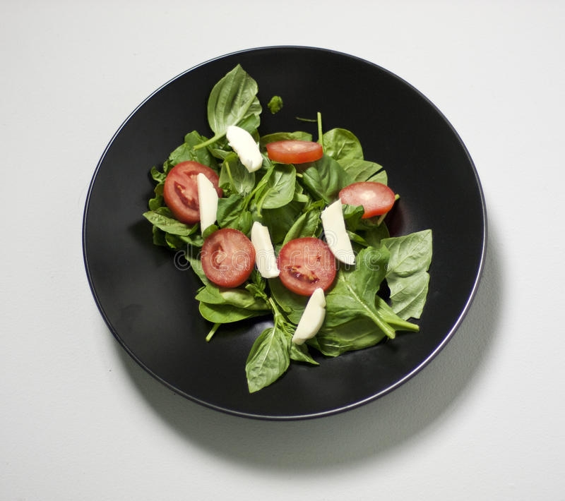 Caprase salad. A Caprase salad on a black plate, on a light gray background. Salad contains tomato, mozzarella cheese and bazil stock photo