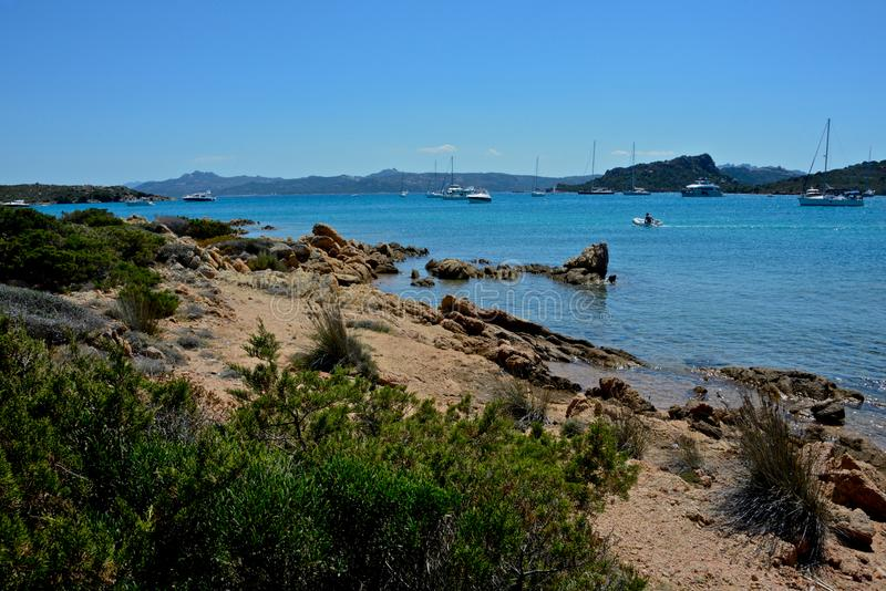 Seascape with blue sea and sky and some rocks and sailing boats moored stock photos