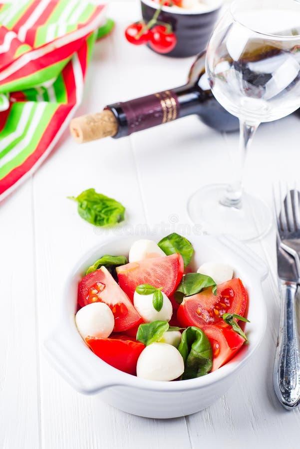 Caprese沙拉用无盐干酪、蕃茄、蓬蒿和香醋在木背景的白色碗安排了 库存照片