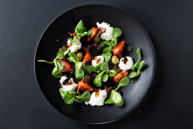 Caprese沙拉用无盐干酪、蕃茄、蓬蒿和香醋在黑色的盘子和黑暗的背景安排了 顶视图 免版税库存图片