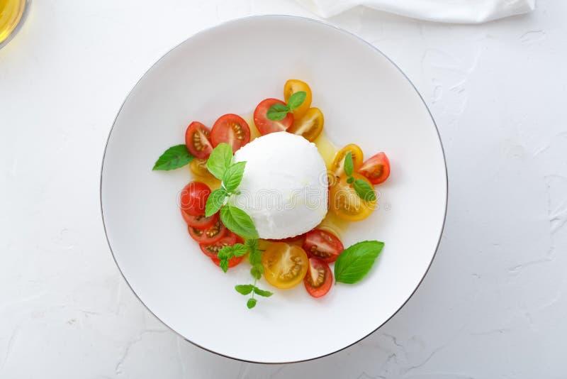 Caprese沙拉用红色和黄色蕃茄、mozarella、蓬蒿和橄榄油 接近的视图 白色背景顶视图 库存图片