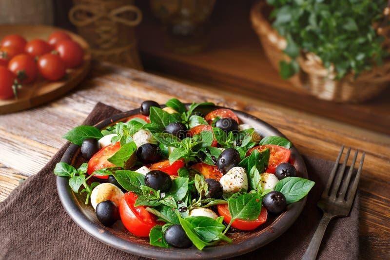 Caprese με τη μοτσαρέλα, τις ντομάτες, το βασιλικό και τις ελιές Κλασική ιταλική σαλάτα στοκ εικόνα με δικαίωμα ελεύθερης χρήσης