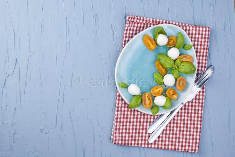 Caprese Классический итальянский салат с томатами вишни и моццареллой vegetarian Голубые предпосылка и открытый космос для текста стоковое изображение