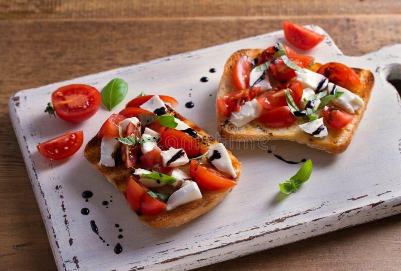 Caprese bruschetta 蕃茄,蓬蒿,与芳香抚人的减少毛毛雨的无盐干酪乳酪在多士 库存照片