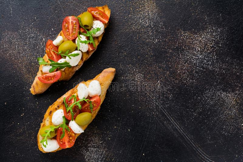 Caprese bruschetta toasts avec tomates cerises, mozzarella, olives et basilic sur fond sombre photo stock