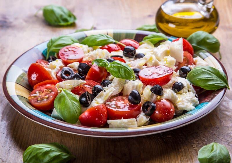 Caprese. Caprese salad. Italian salad. Mediterranean salad. Italian cuisine. Mediterranean cuisine. Tomato mozzarella basil leaves black olives and olive oil royalty free stock photo