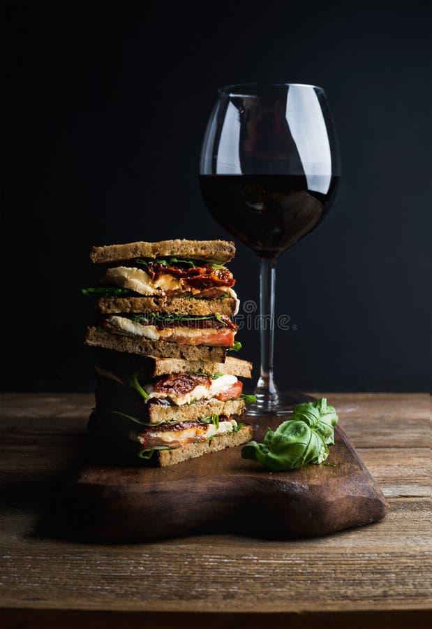 Caprese kanapka, panini lub szkło czerwone wino Całość zbożowego chleba, mozzarella, wysuszeni pomidory, basil Być może obraz royalty free