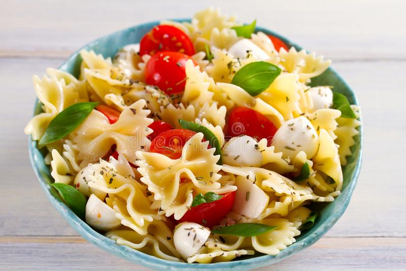 Caprese Pasta Salad. Pasta with mozzarella cheese, tomatoes and basil. stock photography