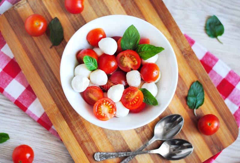 Caprese sałatka z czereśniowymi pomidorami, mozzarellą i basilem, zdjęcia royalty free