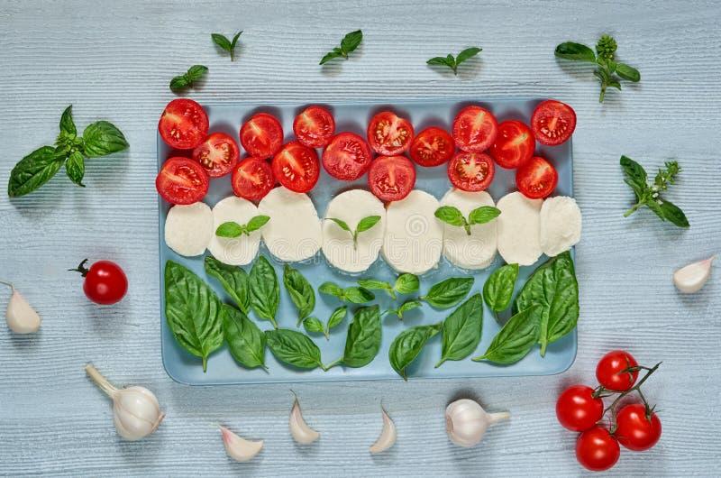 Caprese sałatka z organicznie składnikami: mozzarella ser, czereśniowi pomidory, świeży basil opuszcza, czosnek karmowy włoski tr zdjęcia royalty free