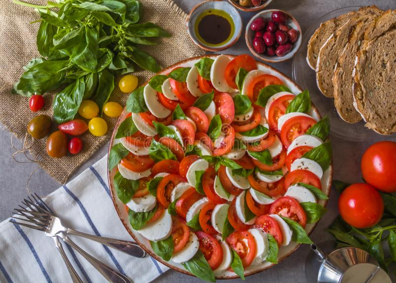 Caprese salad - made of sliced fresh mozzarella, tomatoes, sweet basil leaves, with Olives, balsamic vinaigrette forks and bread royalty free stock photography