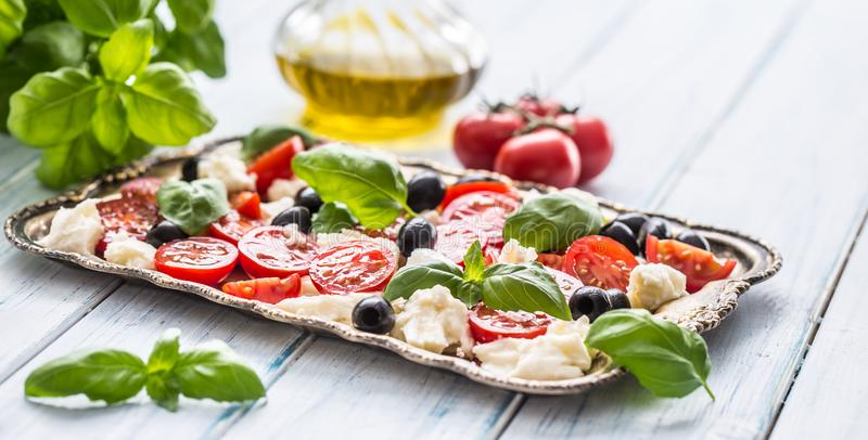 Caprese salad with mozzarella cheese ripe tomatoes olives and basil leaves. Italian or mediterranean healthy meal royalty free stock photos