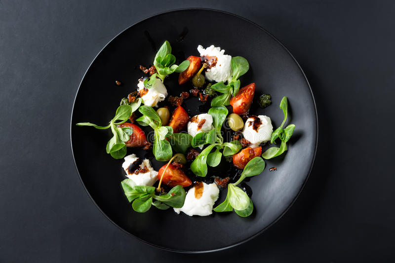 Caprese salad with mozzarella, tomato, basil and balsamic vinegar arranged on black plate and dark background. Top view royalty free stock image