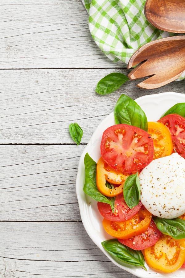 Caprese-Salat mit Tomaten, Basilikum und Mozzarella stockfotografie