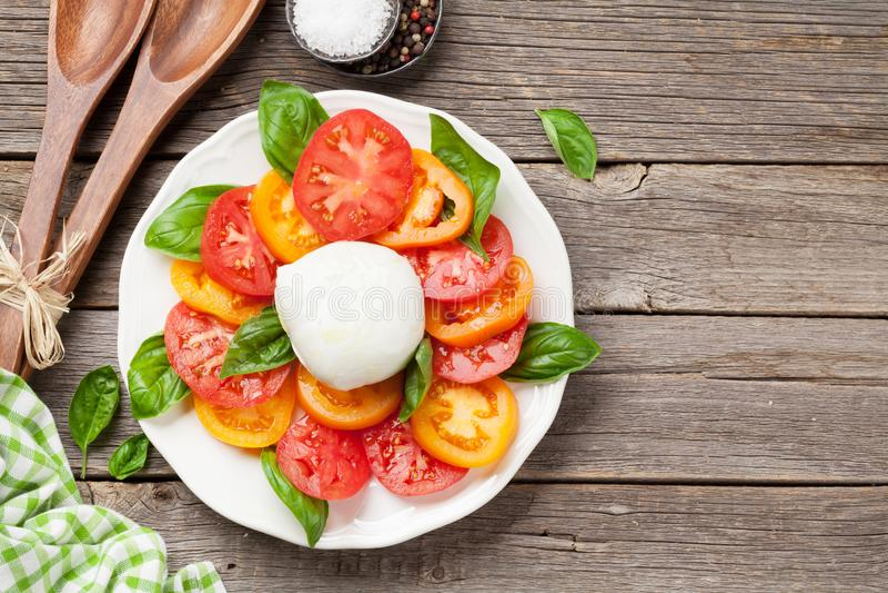 Caprese-Salat mit Tomaten, Basilikum und Mozzarella lizenzfreie stockfotografie