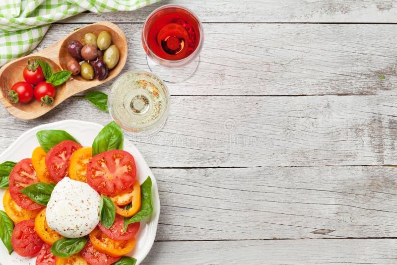 Caprese-Salat mit Tomaten, Basilikum und Mozzarella mit Wein stockfotografie