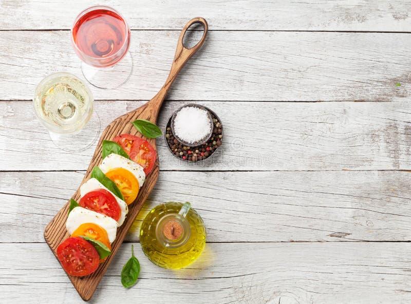Caprese-Salat mit Tomaten, Basilikum und Mozzarella mit Wein lizenzfreies stockfoto