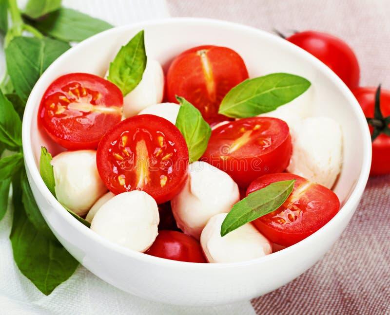 Caprese sallad med mozzarellaen, tomat, basilika på den vita plattan vin arkivbilder
