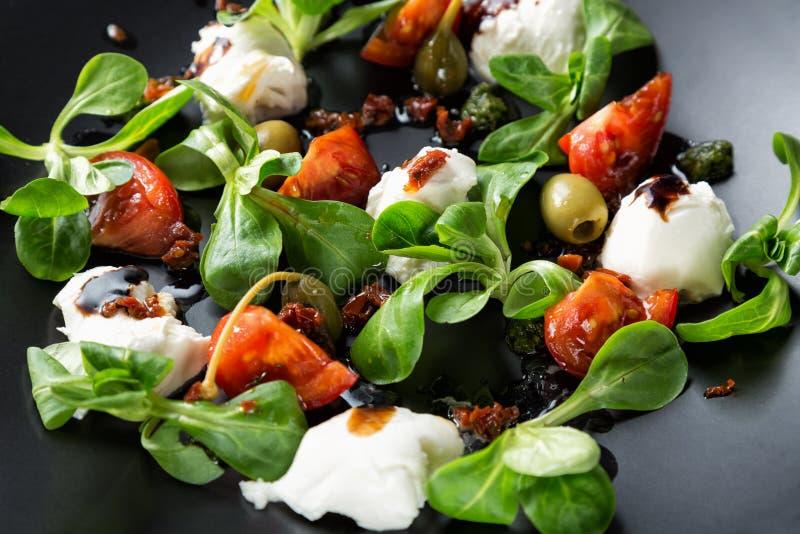 Caprese sallad med mozzarellaen, tomaten, basilika och balsamic vinäger som är ordnade på den svarta plattan Övre bild för slut m royaltyfri bild