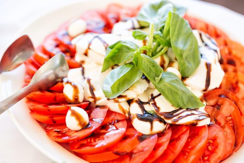 Caprese sallad med mozzarellaen, tomaten, basilika och balsamic vinäger som är ordnade på den vita plattan royaltyfri foto