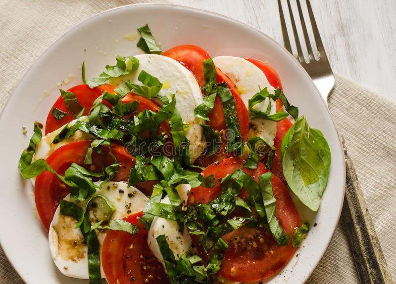 Caprese sallad med tomater, basilika och mozzarellaost arkivbilder